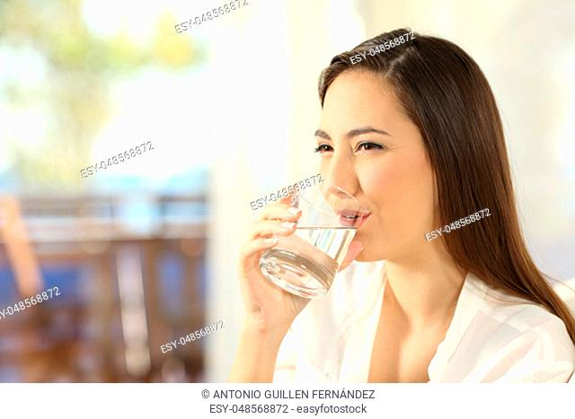 Happy woman drinking water in a glass sitting on a sofa in the living room of a house interior