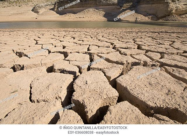 detail of ground with cracked dry land and low level water pond, extreme drought in Entrepenas reservoir, in Guadalajara, Castilla, Spain Europe
