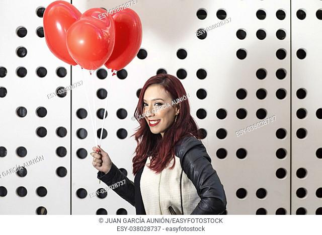 Lovely fashion girl with Valentine heart balloons. Sweet young woman with two heart shaped balloons on white dotted background
