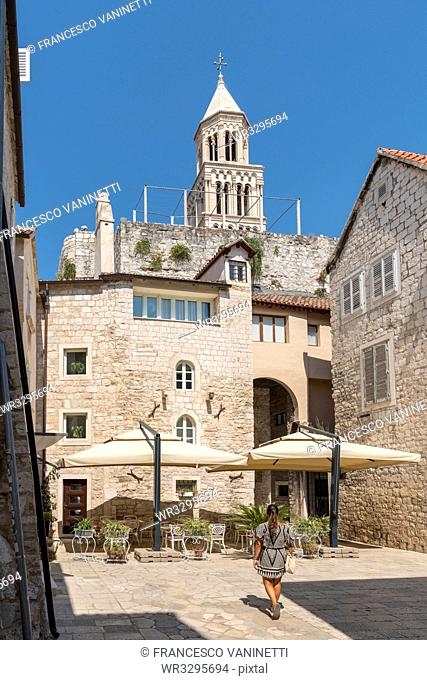 Woman walking in summer, with the bell tower of St. Domnius Cathedral in the background, Split, Split-Dalmatia county, Croatia, Europe