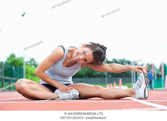 Smiling woman stretching her legs on a track