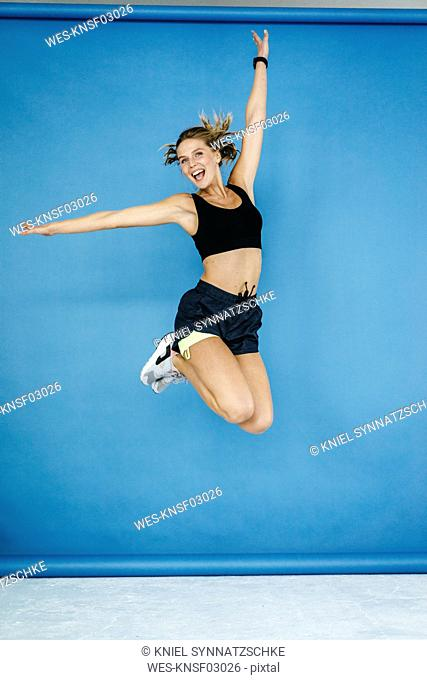 Happy young woman in sportswear jumping midair
