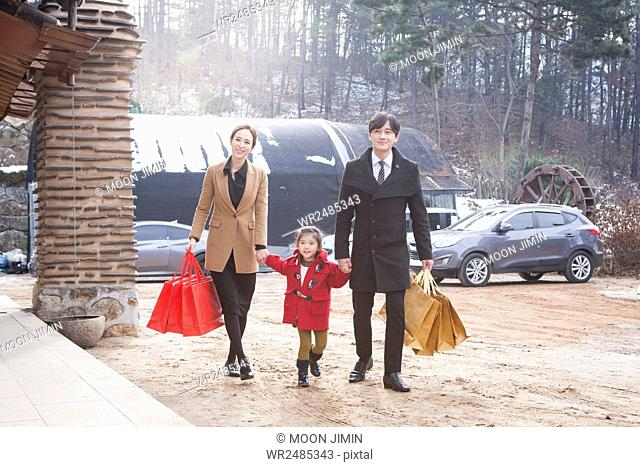 Happy family with shopping bags visiting their hometown