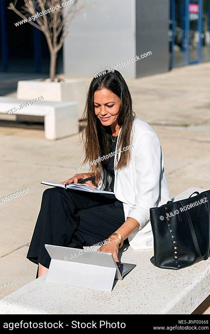 Mature businesswoman with book using digital tablet on sunny day