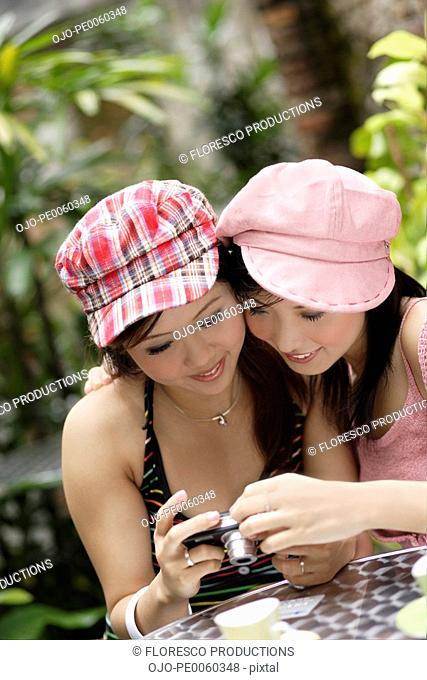 Two women on outdoor patio looking at digital camera