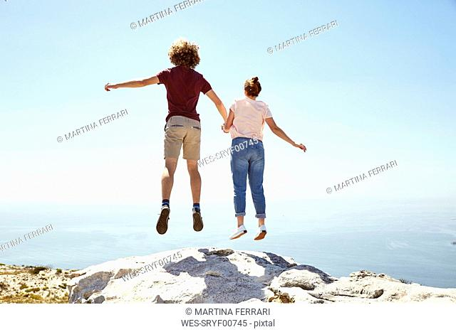 South Africa, Cape Town, young couple jumping on top of a mountain at the coast