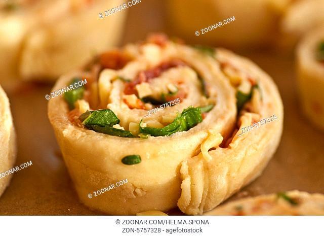 herzhafte Pizza-Schnecken mit Käse, Speck, Bärlauch und Tomate auf weißem Porzellanteller