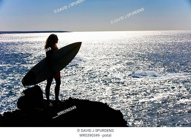 A blond surfer looks out over the ocean at the end of the day