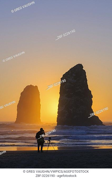 Man photographing The Needles at Haystack Rock in Cannon Beach on the northern Oregon Coast