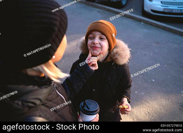 Young mother with son eat street food at winter time and have a fun