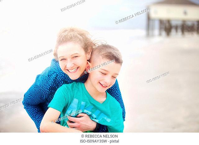 Woman hugging boy on beach