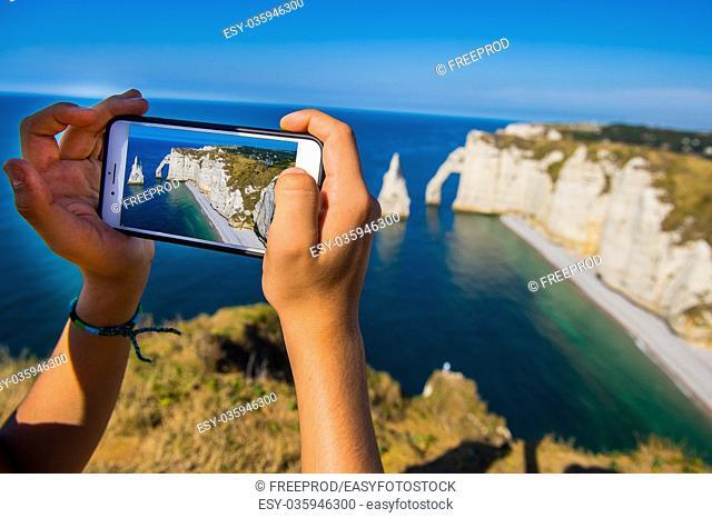 Smartphone in hand photographing, Chalk cliffs Cote d'Albatre. Etretat Normandie France, Europe