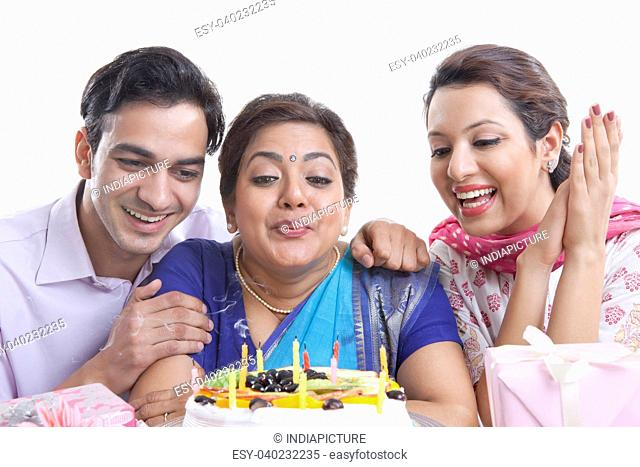 Woman blowing out candles on a birthday cake
