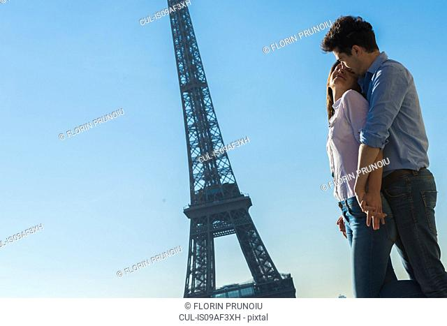 Young couple embracing near Eiffel Tower, Paris, France