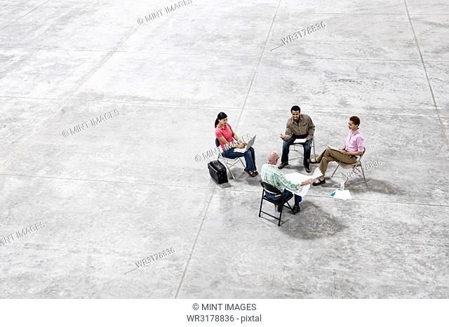 Multi-racial team of people going over plans for a new warehouse interior