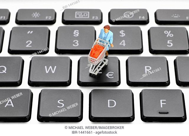 Miniature figure with cart on keyboard, euro symbol, symbolic picture for online shopping