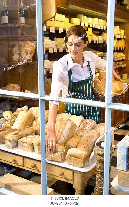 Saleswoman arranging fresh loaves of bread in cheese shop window