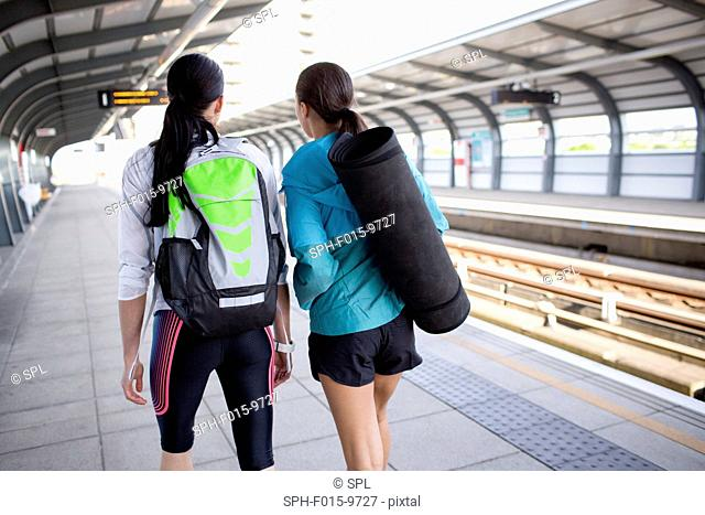 MODEL RELEASED. Two young women with sports equipment on railway platform