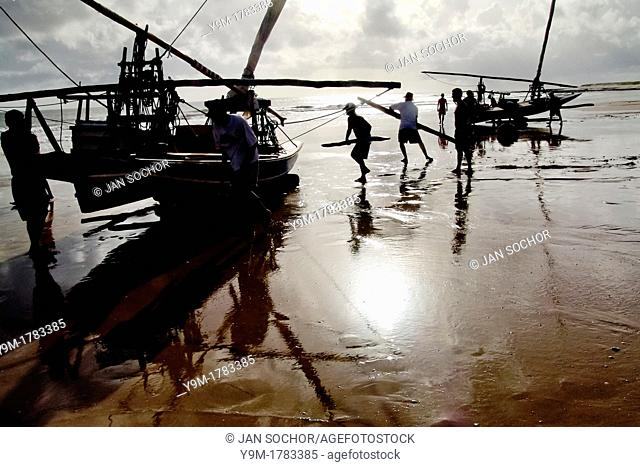 Brazilian fishermen pushing their boat by hands towards the ocean during the sunrise in Uruau, state Ceara, Brazil, 16 March 2004  Fishermen use a unique wooden...