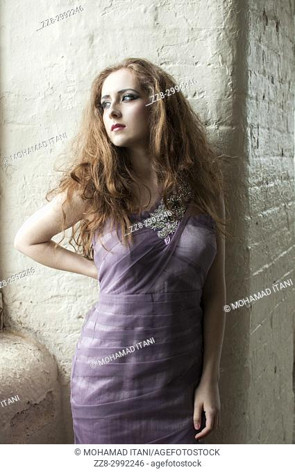 Portrait of a beautiful redhead woman wearing a dress looking away