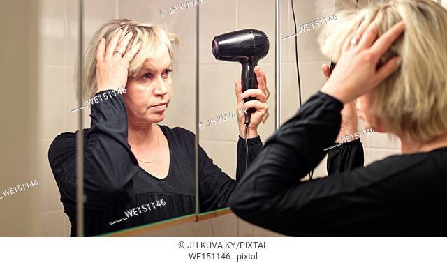Mature woman used hair dryer in bathroom