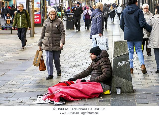 Homeless street beggar sitting on rugs, Sauchiehall Street, Glasgow, Scotland