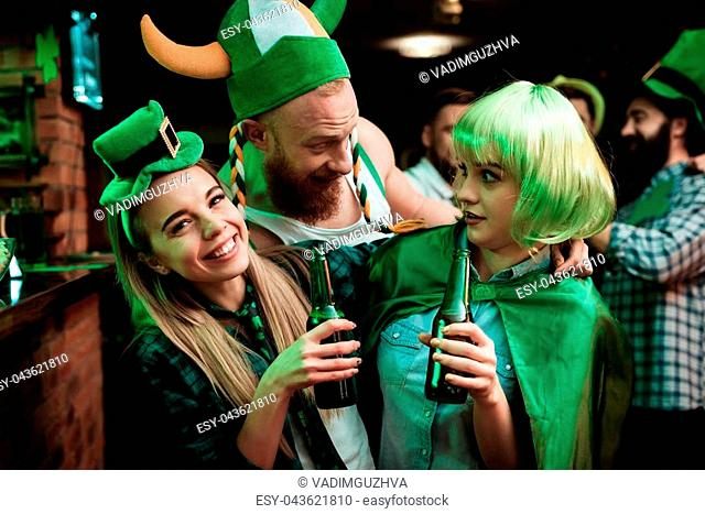 Man in a Viking hat flirting with two girls. She celebrates St. Patrick's Day at the pub