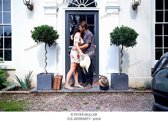 Romantic couple hugging each other at hotel front door