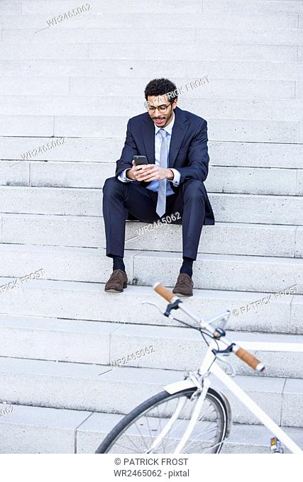 Businessman with bicycle using smart phone in city