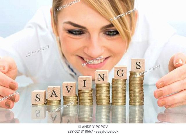 Close-up Of Businesswoman Covering Savings Wooden Block On Stacked Coins With Hands