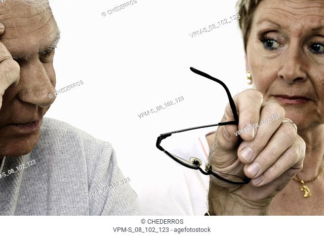 Close-up of a senior woman looking at a senior man with his hand on his temple