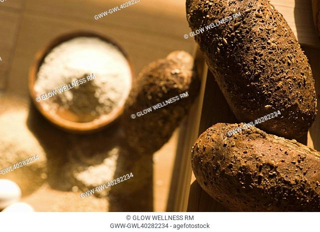 Close-up of breads with a bowl of flour