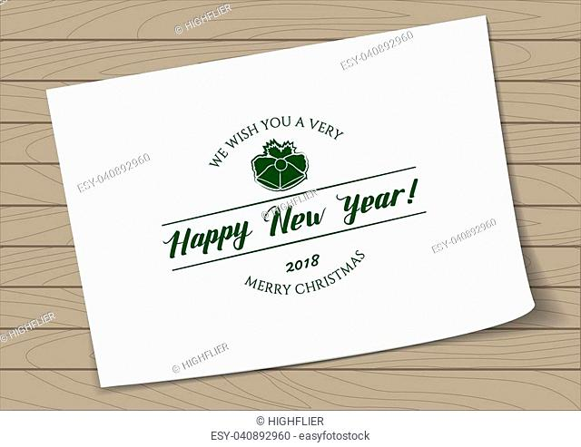 Badge Merry Christmas and Happy New Year with Hand Drawn Lettering and Bells Icon on A4 Sheet Paper on Wooden Background