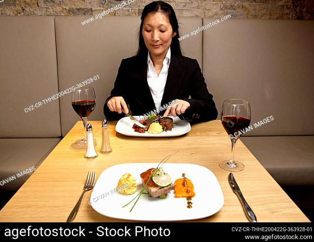 Businesswoman eating at restaurant in a luxury hotel