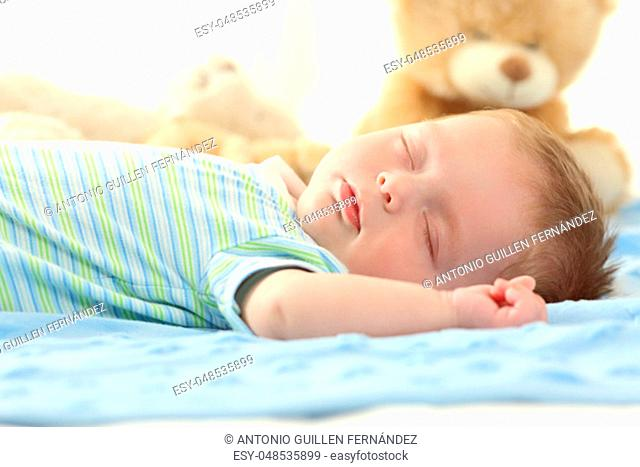 Portrait of a single baby sleeping on a bed