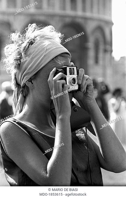 A young tourist photographing the monuments of piazza del Duomo. In the background, the Baptistry of St. John. Pisa, 1963