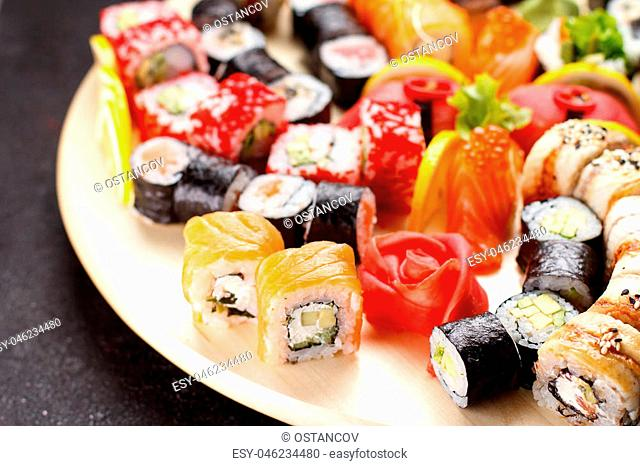 Japanese cuisine. Sushi set on a round wooden board over black concrete background