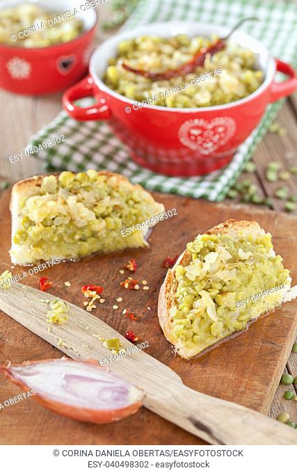 Cream made with stuffed green split peas and sauce of olive oil and fried onions, served on bread slices