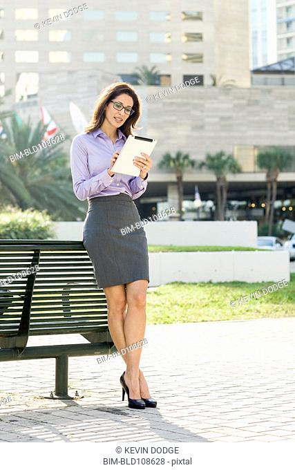 Hispanic businesswoman leaning on bench using digital tablet