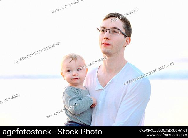 A young father holding his son while the sun sets at the beach