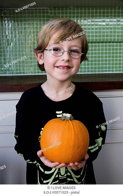 Little boy holding an orange Hallowe'en pumpkin