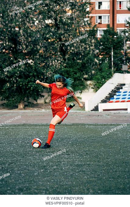Young woman playing football on football ground shooting the ball