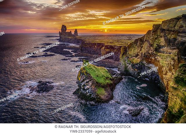 Londrangar sea stacks and the Thufubjarg cliffs. Londrangar are basalt volcanic dikes that were formed after magma solidified and after years of erosion these...
