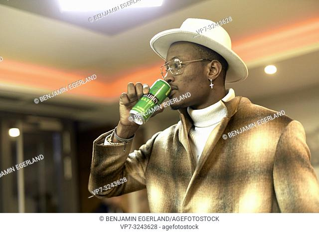 stylish blogger man drinking energy drink indoors in bar, wearing men's fashion clothing outfit, side view upper body, Christian cross earring, in Munich