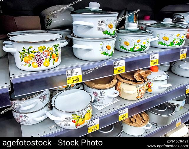 Samara, Russia - September 26, 2019: Different metal enamelware, cooking pots containers utensils for sale on store shelf