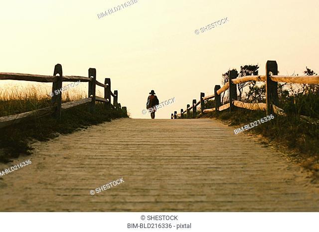 Silhouette of woman walking on wooden walkway