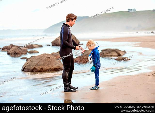 Father and son in wetsuits on beach in New Zealand