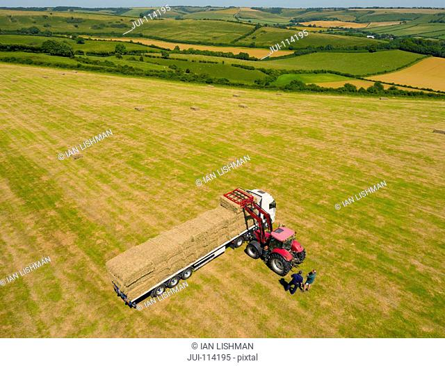 Aerial View Of Stacking Hay Bales Onto Lorry In Field