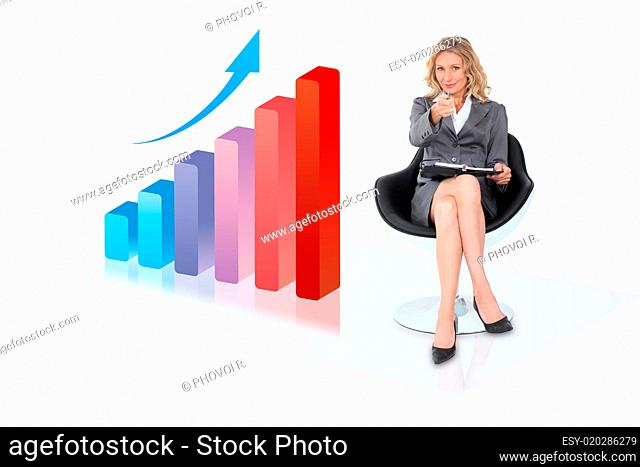 Businesswoman sitting by bar chart