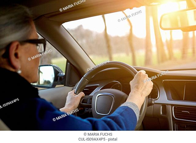 Over the shoulder view of woman in car driving on tree lined road